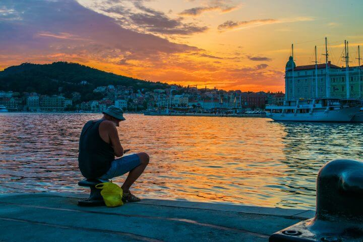 guide to Split Sunsets: where to watch the sunset in split, fisherman watching the sunset from the port